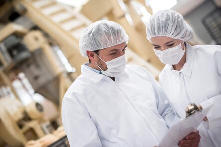 Two food service manufacturing employees conversing