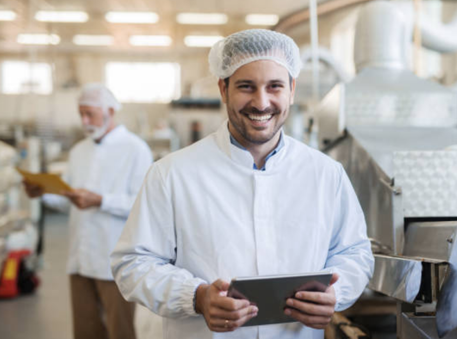 Man smiling while working at a food manufacturing plant